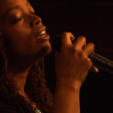 A picture of Dara Tucker singing with a microphone in her hand
